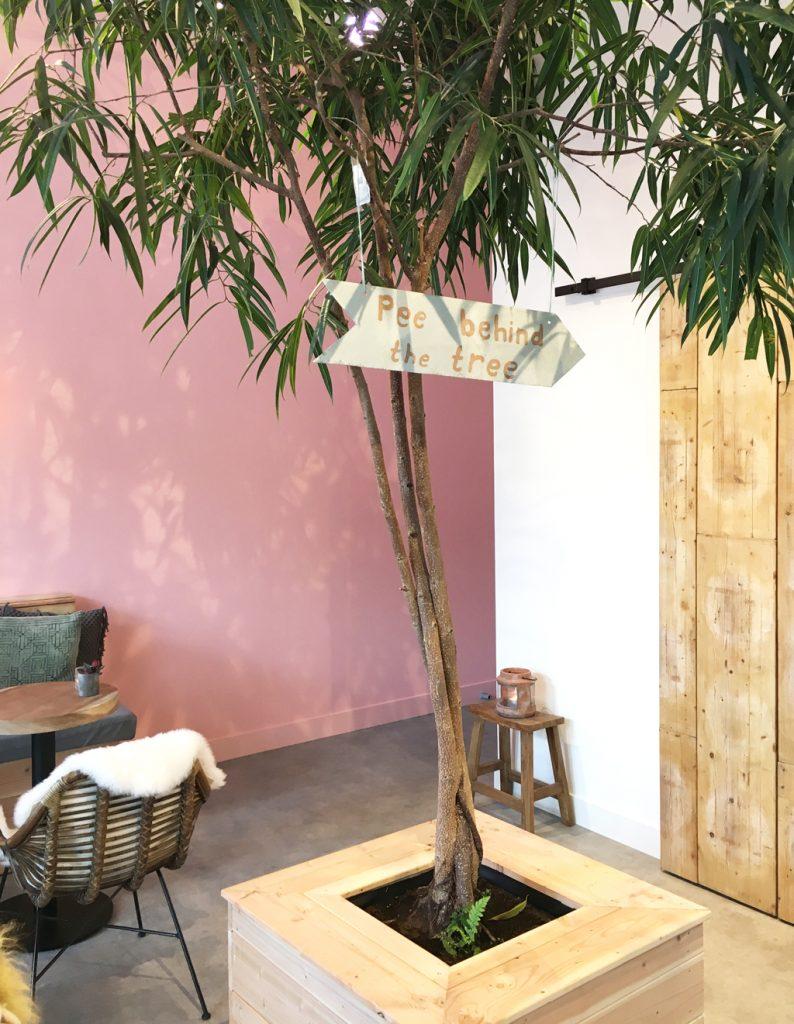 Pee behind the tree bord bij Lot & Daan met roze muur als achtergrond